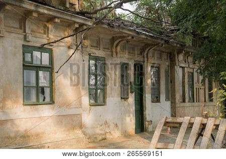 Old Destroyed Stone House On The Yard With Trees Around. Poverty And Misery, South, Summer