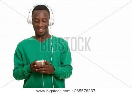 Young Happy African Man Smiling And Using Mobile Phone While Lis