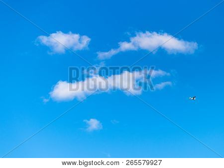 Blue Sky With White Fluffy Clouds In The Shape Of A Smiling Face