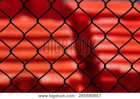 Abstract Chain Link Fence With Red In The Distance