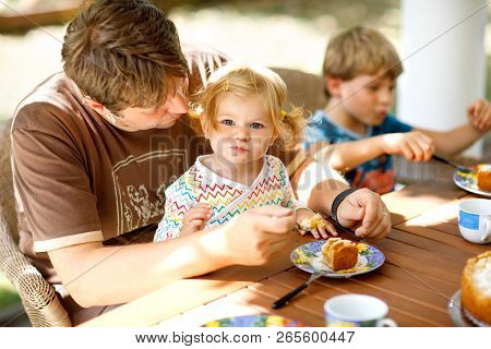 Young Middle-aged Father Feeding Cute Little Toddler Girl In Restaurant. Kid Boy Eating On Backgroun