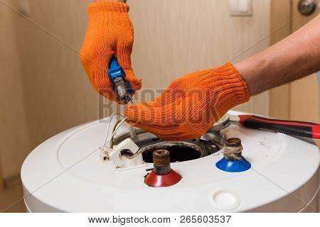 Plumber With Pliers Fix Wires Of Water Heater