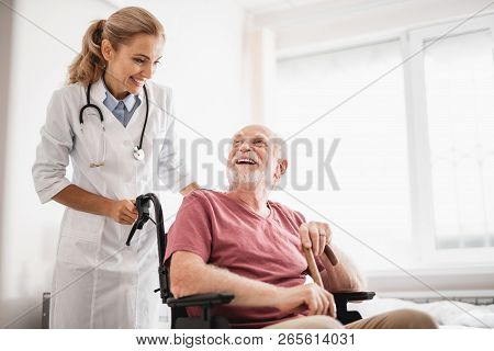 Old Bearded Man Sitting In Wheelchair While Doctor Standing Behind