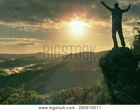 Crazy Man At Edge. Fearless Hiker On Cliff Above Deep Hole. Morning Or Evening Sun Close To Horizon.