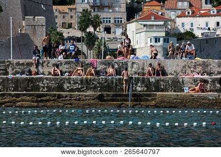 Dubrovnik, Croatia, July 31, 2018: Tourists And Locals Sunbathing On The Dubrovnik St John Fort Pier