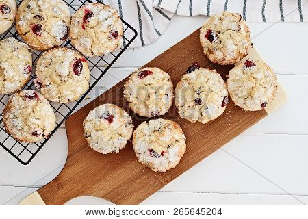 Fresh Cranberry Muffins Cooling On A Bakers Rack And A Wood Cutting Board Over A Rustic White Table