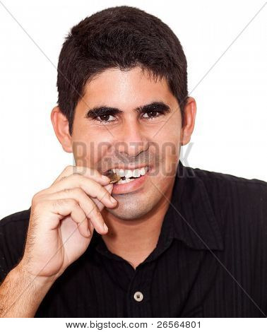 Young latin man biting a coin to verify its authenticity on a white background