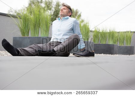 Senior business man with his shoes off sitting on the ground relaxing and closing his eyes