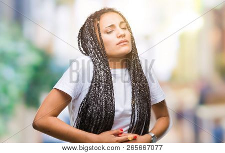 Young braided hair african american girl over isolated background with hand on stomach because indigestion, painful illness feeling unwell. Ache concept.