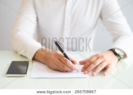 Closeup Of Man Working And Writing On Sheet Of Paper. Paper Sheet And Smartphone Lying On Desk. Appl