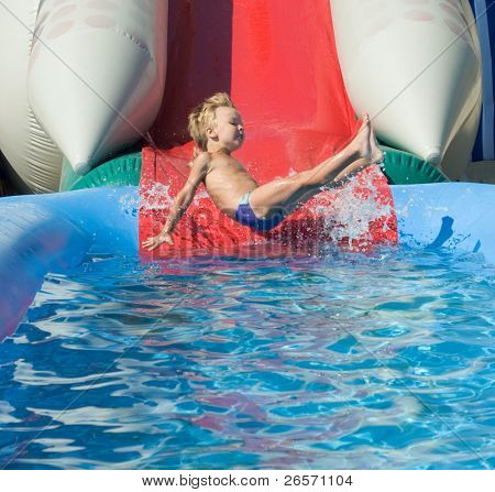 Young boy on water slide at a vacation resort