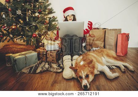 Happy Girl In Santa Hat Shopping Online On Laptop And Sitting With Cute Dog At Golden Beautiful Chri