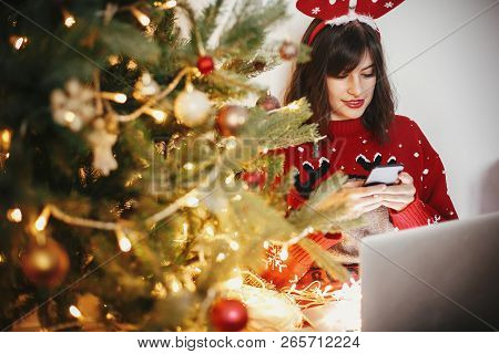 Beautiful  Girl In Reindeer Antlers Browsing Phone And Sitting With Laptop At Golden Christmas Tree
