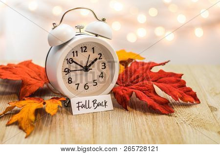 Fall Back Daylight Saving Time Concept With White Clock And Autumn Leaves, Soft Bokeh Background On