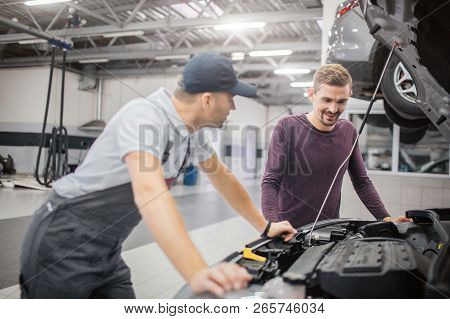 Worker And Owner Of Car Stand At Opened Front Body Of Vehicle. Bearded Man Look At It. Worker Leans