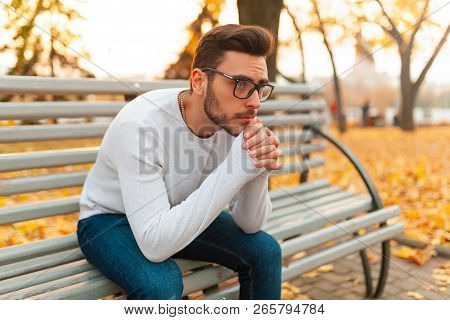 A Lonely Handsome Man Sits Sad In The Park On A Bench. Autumn Season, Yellow Leaves On Background. L