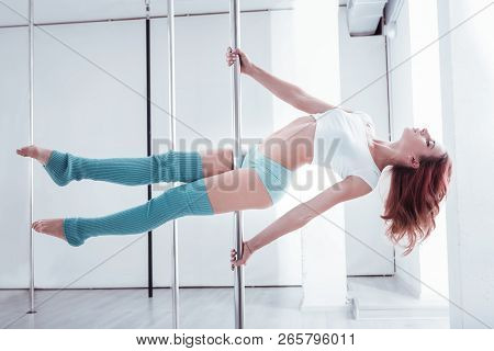 Strong And Fit Red-haired Pole Dancer Making Pole Flow