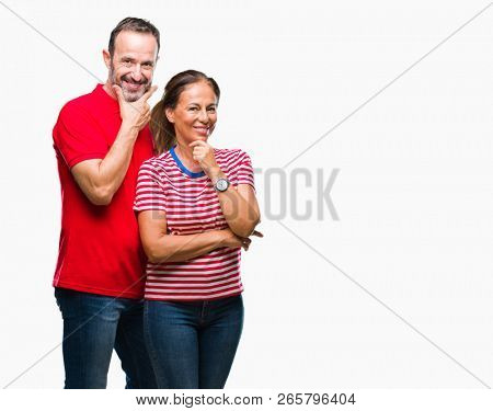 Middle age hispanic couple in love over isolated background looking confident at the camera with smile with crossed arms and hand raised on chin. Thinking positive.