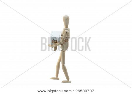 A Wooden Manikin Holding Christmas Package