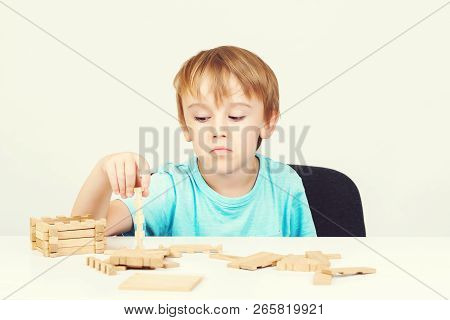 Sad Child Sitting At Table. Child Plays With Construction Toy Blocks At The Table. Sad Bored Boy Bui
