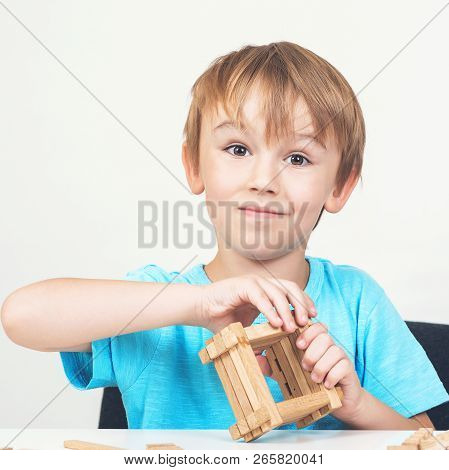Funny Kid Builds Small Wooden House. Eco House. Construction Concept. Little Boy Plays With Blocks.