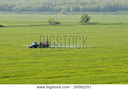 Aerial View Of Tractor Spraying Substances Over Green Crops Field