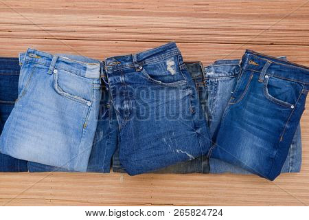 Jeans. Stylish clothes. Selective focus on wooden background