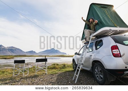 Hofn, Iceland - August 2018: Young Bearded Man Sitting And Stretching In A Roof Top Tent Mounted On