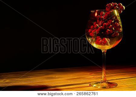 A Bunch Of Ripe Grapes In A Glass Glass Glass On A Wooden Table And A Black Background.