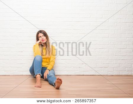 Young adult woman sitting on the floor over white brick wall with hand on chin thinking about question, pensive expression. Smiling with thoughtful face. Doubt concept.