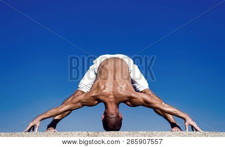Yoga Practice Helps Find Harmony And Balance. Man Practicing Yoga Blue Sky Background. Reached Peace