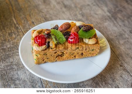 Delicious Dried Fruit Cake With Almond And Cashew Nut On White Plate And Wood Table.