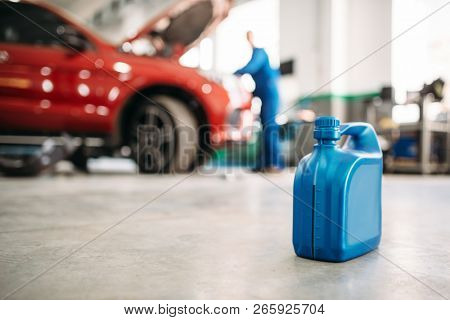 Oil canister on the floor in car service