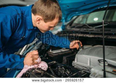 Male technician checks brake fluid level in car