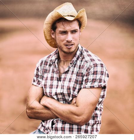 Cowboy hat sexy handsome american man in USA countryside farm. Farmer in plaid shirt serious looking attractive.