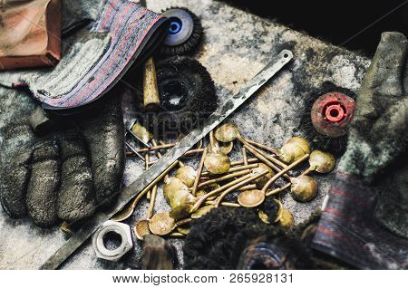 Top view of different goldsmiths tools on the jewelry workplace. Desktop for craft jewelry making with professional tools. Aerial view of tools over rustic wooden background. poster