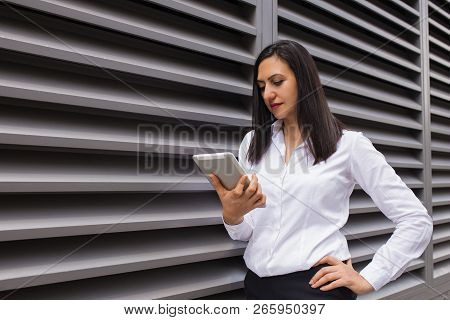 Portrait Of Confident Young Businesswoman Using Digital Tablet. Caucasian Female Student Networking