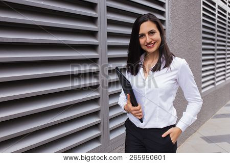 Portrait Of Happy Businesswoman Walking With Folder Outdoors. Caucasian Woman Standing At Office Bui