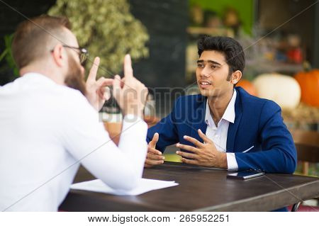 Multi-ethnic Men Arguing While Discussing Project In Cafe. Confident Young Indian Male Manager Gestu
