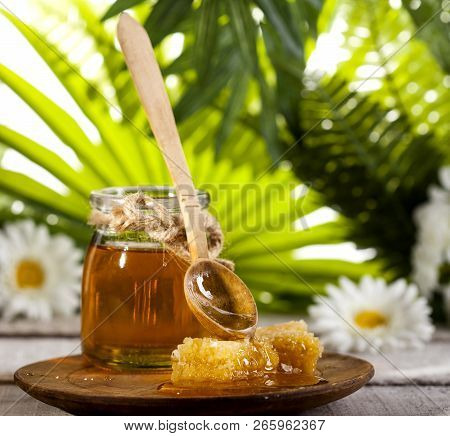 Glass Jar Of Honey With Wooden Drizzler And Chamomile