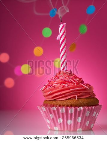 Festive Cupcake With Candle And Cream On A Pink Background Decorated With Colorful Confetti