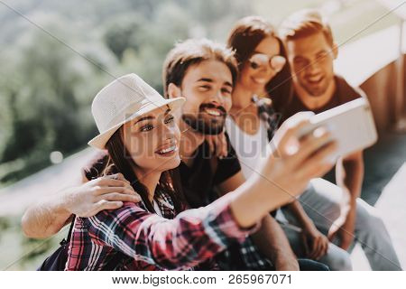 Young Smiling People Sitting In Park Taking Selfie. Group Of Young Friends With Backpacks Sitting To