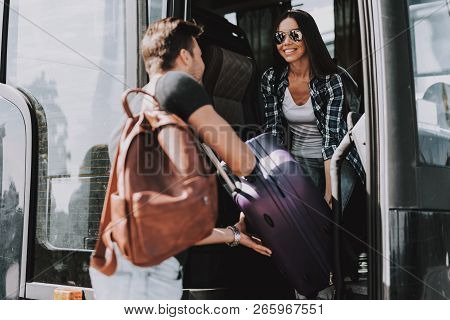 Smiling Young Couple Boarding On Travel Bus. Handsome Man And Beautiful Woman Carrying Luggage To Bu