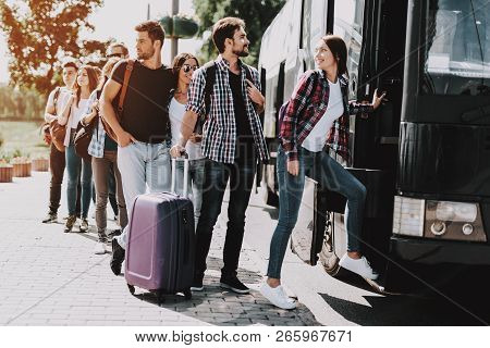Group Of Young People Boarding On Travel Bus. Happy Travelers Standing In Queue Holding Luggage Wait