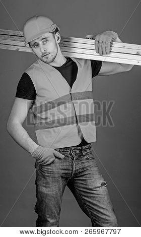 Carpenter, Woodworker, Labourer, Builder On Confident Face Carries Wooden Beams On Shoulder. Man In