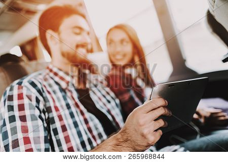 Smiling Couple Using Digital Tablet In Tour Bus. Young Handsome Man And Beautiful Woman Sitting On P