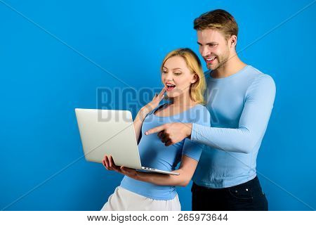 Couple Surfing On Internet With Laptop. Pc. Happy Couple With Laptop. Stylish Guy Hugs Girl. Modern