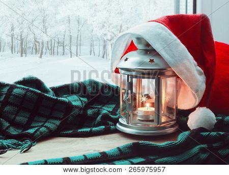 Festive tranquil Christmas and New Year still life -lantern with candle and Santa hat on the windowsill and winter park outdoor. Concept of Christmas and New Year.Christmas and New year still life. Christmas composition