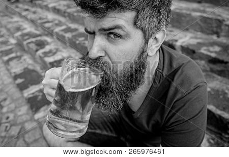 Guy having rest with cold draught beer. Hipster on calm face drinking beer outdoor. Man with beard and mustache holds glass with beer while sits on stone stairs. Draught beer concept poster