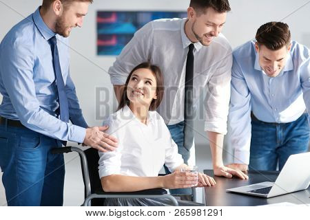 Young woman in wheelchair with colleagues at workplace